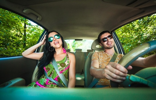 Young Couple Driving Along Country Road.